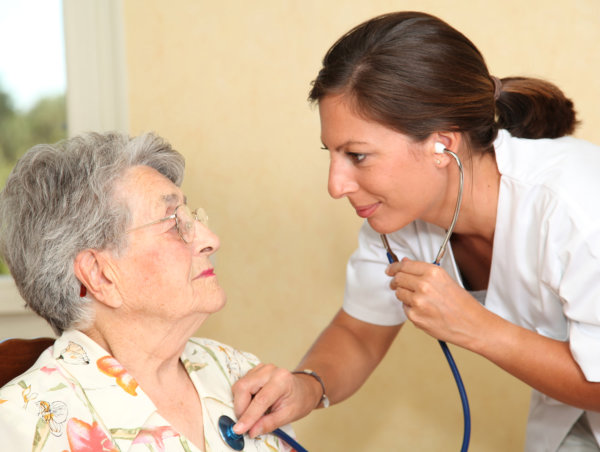 Nurse checking blood pressure of elderly