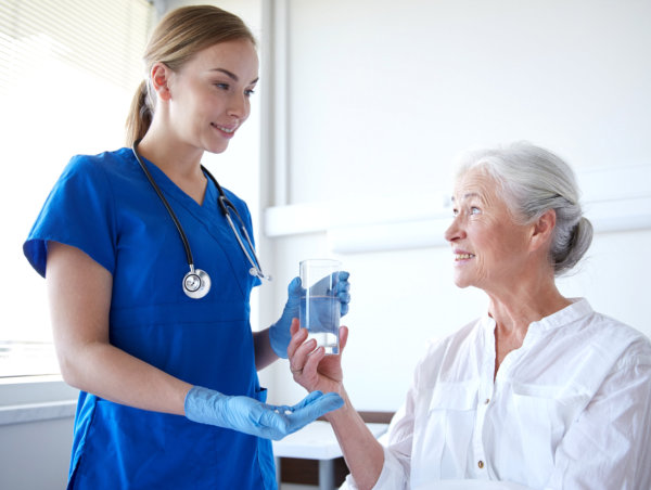 Nurse handing medicine to elderly woman