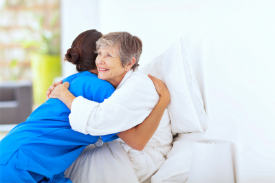 Happy elderly women hugging caregiver on bed