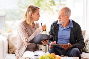 caregiver talking to an elderly man