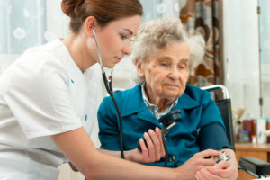 nurse checking on elderly woman