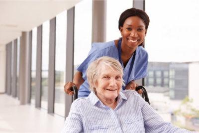elderly woman in wheelchair with her caregiver